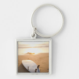 Surfboard laying on beach at sunset Silver-Colored square key ring