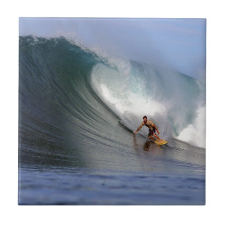 Surfer surfing huge tropical island surfing wave small square tile
