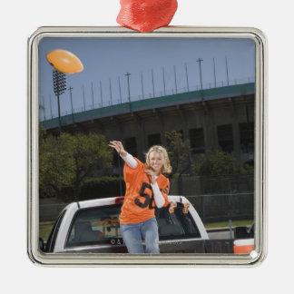 Tailgating woman throwing football christmas ornament
