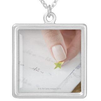 Teacher affixing gold star to math worksheet necklace