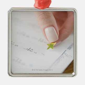 Teacher affixing gold star to math worksheet Silver-Colored square decoration