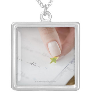 Teacher affixing gold star to math worksheet silver plated necklace