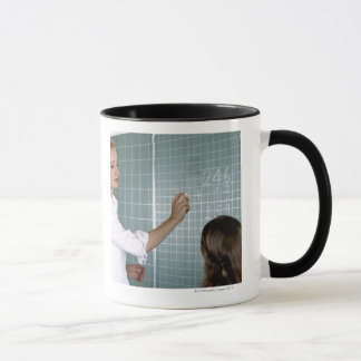 teacher and young girl in front of blackboard in mug