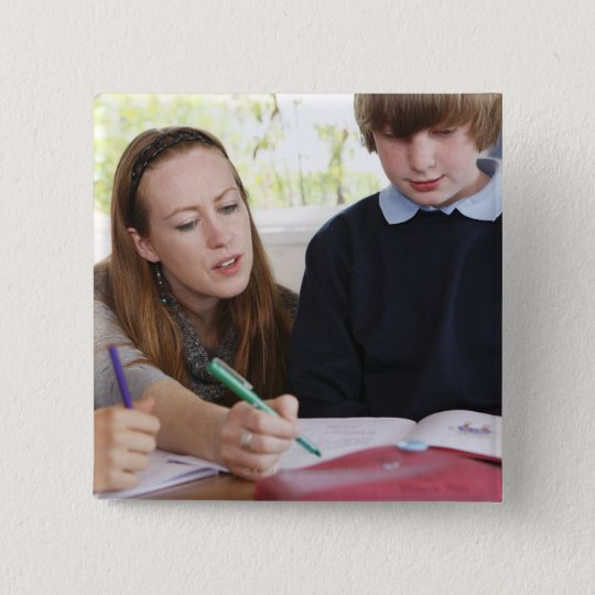 teacher assisting child with work in classroom 15 cm square badge