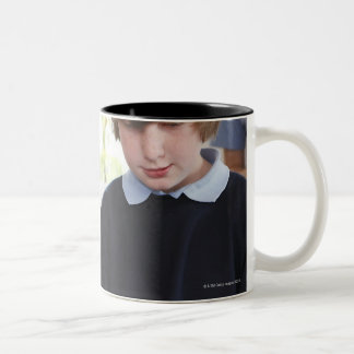 teacher assisting child with work in classroom Two-Tone coffee mug