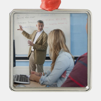 Teacher at whiteboard explaining lesson to Silver-Colored square decoration