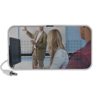 Teacher at whiteboard explaining lesson to iPod speakers