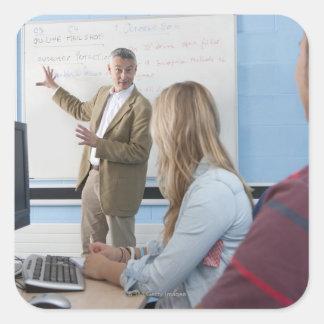 Teacher at whiteboard explaining lesson to square sticker