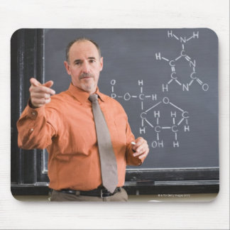 Teacher by chalkboard with structure of chemical mouse pad
