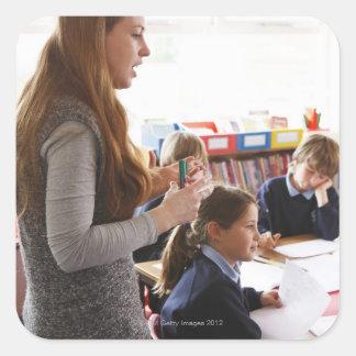 teacher explaining lesson to schoolchildren square sticker
