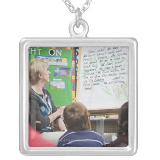 Teacher giving classroom presentation to silver plated necklace