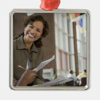 Teacher giving paperwork to student christmas ornament
