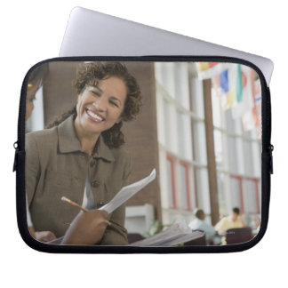 Teacher giving paperwork to student laptop sleeve