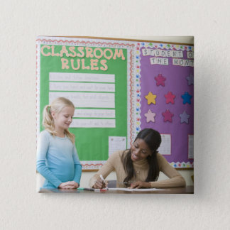 Teacher grading girls paper in classroom 15 cm square badge