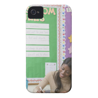 Teacher grading girls paper in classroom Case-Mate iPhone 4 cases