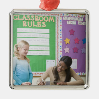 Teacher grading girls paper in classroom christmas ornament