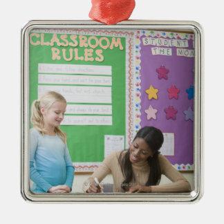 Teacher grading girls paper in classroom christmas ornament
