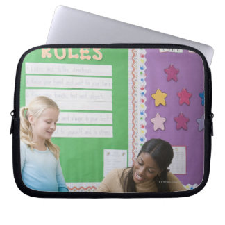 Teacher grading girls paper in classroom laptop sleeve