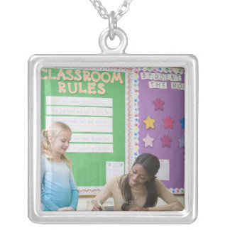 Teacher grading girls paper in classroom silver plated necklace