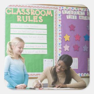 Teacher grading girls paper in classroom square sticker