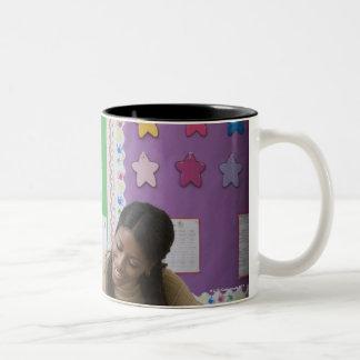 Teacher grading girls paper in classroom Two-Tone coffee mug
