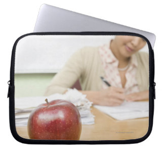 Teacher grading papers with apple in foreground laptop sleeve