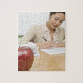 Teacher grading papers with apple in foreground puzzles
