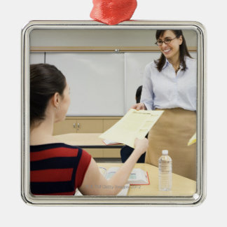 Teacher handing paper back to student christmas ornament