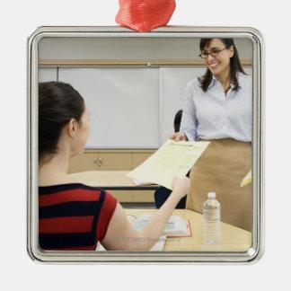 Teacher handing paper back to student christmas ornament
