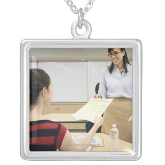 Teacher handing paper back to student silver plated necklace