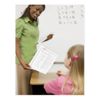 Teacher handing paper to student with A plus Postcard