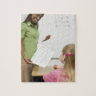 Teacher handing paper to student with A plus Puzzle