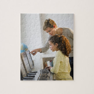 Teacher helping student in computer lab jigsaw puzzle