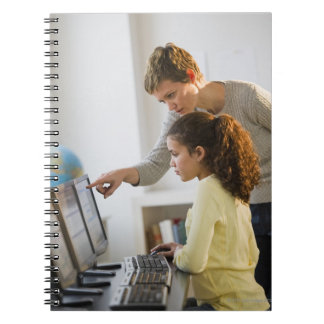 Teacher helping student in computer lab notebook
