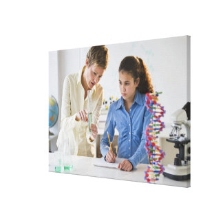 Teacher helping student in science lab canvas print