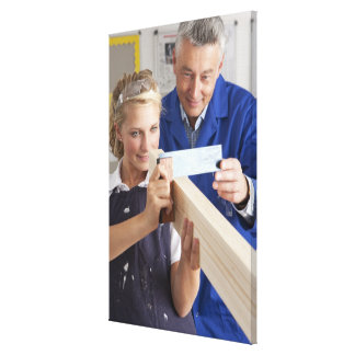 Teacher helping student measuring planed wood in canvas print