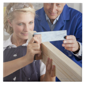 Teacher helping student measuring planed wood in large square tile