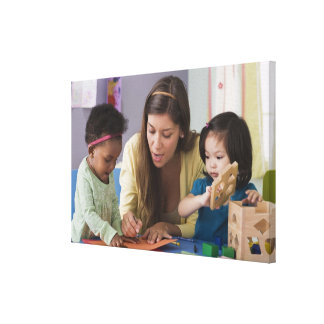 Teacher helping toddlers color at daycare canvas print