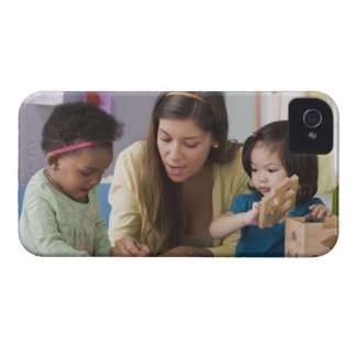 Teacher helping toddlers color at daycare iPhone 4 case