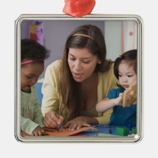 Teacher helping toddlers color at daycare Silver-Colored square decoration