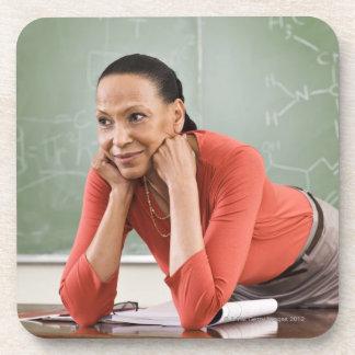 Teacher leaning on desk by chalkboard beverage coaster
