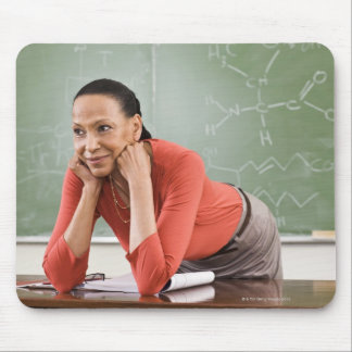 Teacher leaning on desk by chalkboard mouse pad