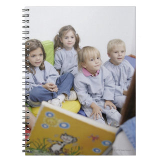 Teacher reading to students notebook