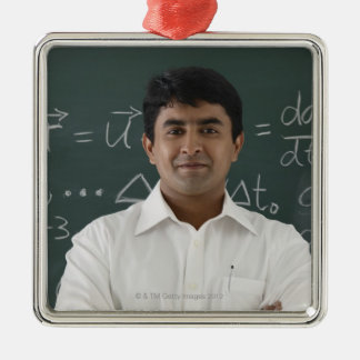 teacher standing in front of chalkboard, arms christmas ornament