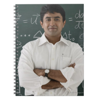 teacher standing in front of chalkboard, arms notebook