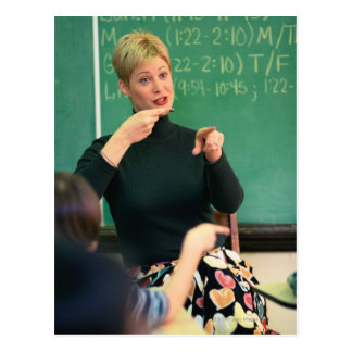 Teacher talking and pointing at front of postcard
