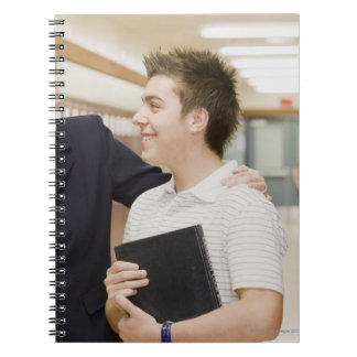 Teacher talking to student, hand on his shoulder notebook