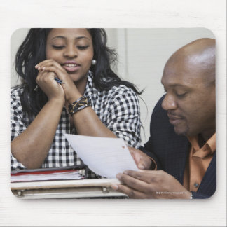 Teacher talking to student in classroom mouse mat