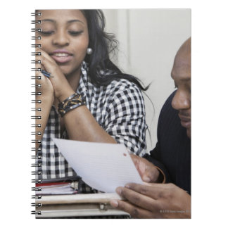 Teacher talking to student in classroom notebook