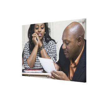 Teacher talking to student in classroom stretched canvas prints